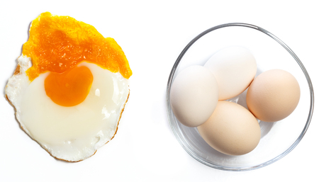 unbreakable: Fried egg on a white background next to a glass bowl with a few healthy unbreakable eggs, concept of being different