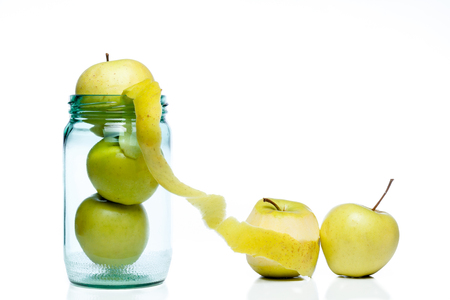 claustrophobia: Glass jar full of apples on a white background, showing concept of escape from usually and a single cleaned apple
