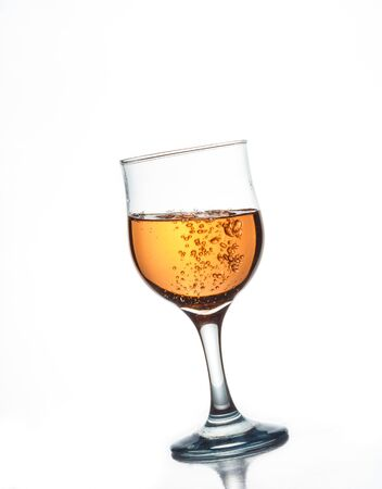 Tilted glass of wine on a white background, sparkling alcoholic beverage
