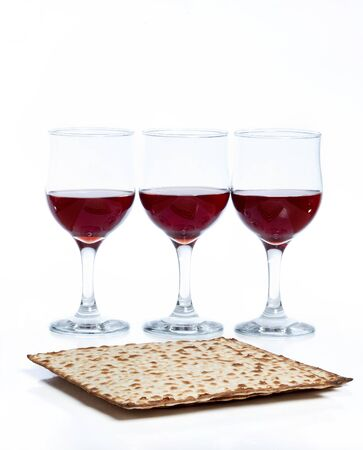 bread and wine: glasses of red wine on white background along with matzos, jewish traditional bread Stock Photo