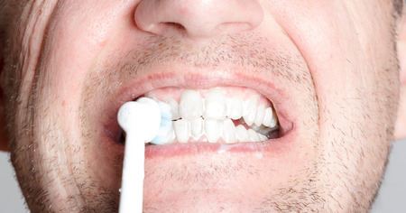 personal hygiene: Close-up of a young man while brushing his teeth, personal hygiene