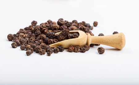 Black peppercor seeds on a white table, wooden scoop and a fabric red bag for storage Stock Photo