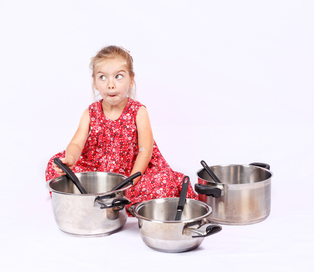 Adorable caucasian little girl isolated on whit background, cooking with silver and coloured pot Stock Photo