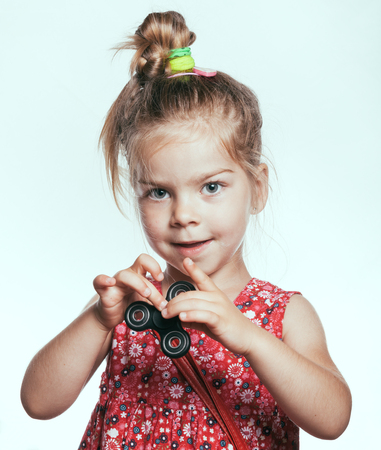 Little girl playing with fidget spinner, on white background. faded color and tonality photo.