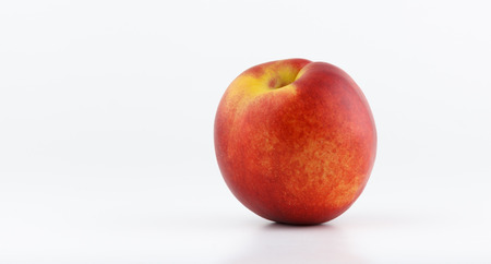 declining: Freash healthy peach isolated on white background, vegan lifestyle Stock Photo