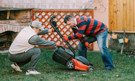 Young neighbour helps senior men with gardnering work around the house Stok Fotoğraf