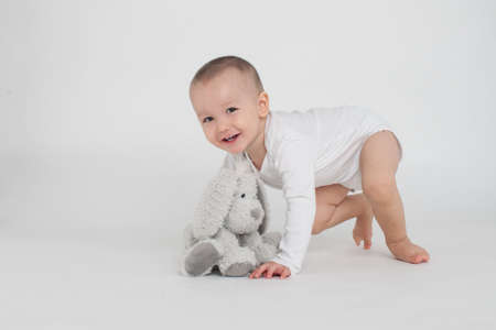 baby on a white background with a soft toy bunny