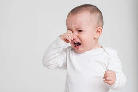 Bebé en un fondo blanco en un pijama blanco Foto de archivo - 62203534