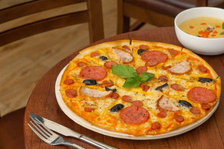 luscious: pizza on the kitchen table with a fork and soup
