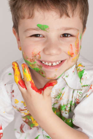 smeared baby: a colorful portrait of a young boy wearing a shirt covered in paint on a light background