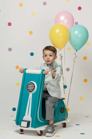 game drive: Boy in costume designer on a toy bike with balloons on a white background