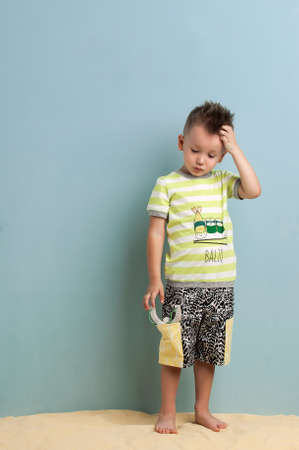 little boy in shorts and a T-shirt with a slingshot in his hands stands on the sand on a light blue background BALIQ - A FISH Stock Photo