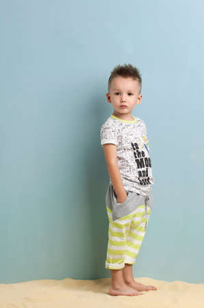 little boy in a shirt and shorts standing on the sand on a light blue background