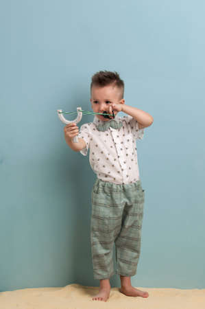colourful tie: little boy in fashionable clothing and a slingshot in his hands stands on the sand on a light blue background