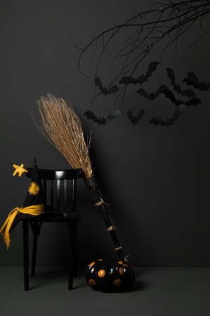 besom: halloween with black bats on a tree with a pumpkin and a hat on a dark background Stock Photo