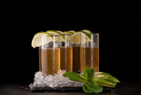 vaso de precipitado: some glasses with yellow citron drink and ice on a black stone on a dark background