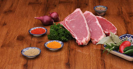 varnished: raw meat with herbs and lettuce and onions with pepper on the varnished board Stock Photo