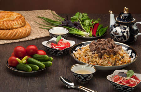 pastil: Eastern pilaf and salads with fresh vegetables, and cake and tea on a wooden board Stock Photo