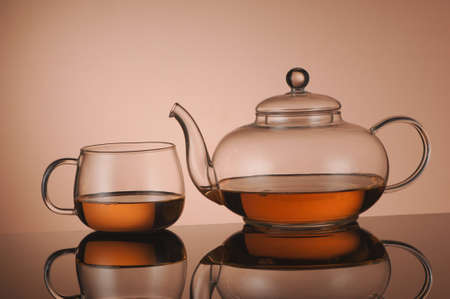 Transparent glass teapot and cup of tea on the reflective surface Stock Photo