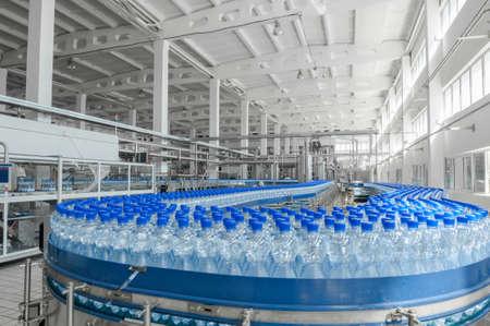 Para la producción de botellas de plástico y botellas en una fábrica de cinta transportadora Foto de archivo - 66475898