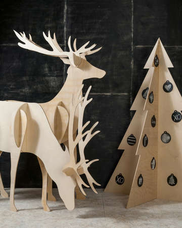 New Years and Christmas decorations and fir plywood deer and a tree on a dark background