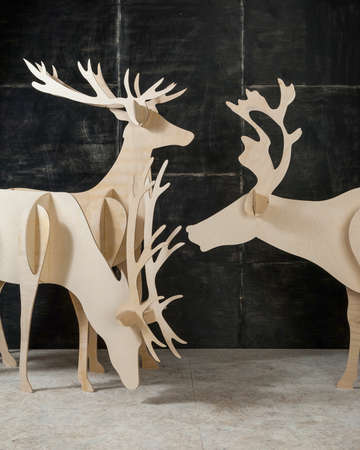 New Years and Christmas decoration deer made of plywood and wood on a dark background