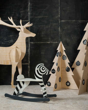New Years and Christmas decoration deer and fir plywood and wood on a dark background