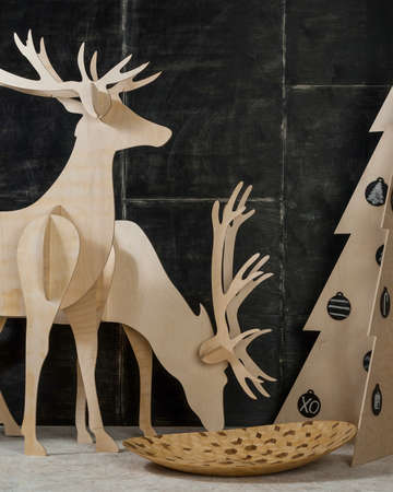 dcor: New Years and Christmas decorations and fir plywood deer and a tree on a dark background
