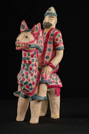burnt: Asian and Oriental painted toy from burnt clay in the form of a man on a horse on a black background Stock Photo