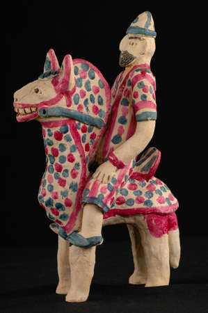Asian and Oriental painted toy from burnt clay in the form of a man on a horse on a black background Stock Photo