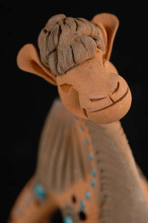burnt: Asian and Oriental painted toy from burnt clay in the form of a camel on a black background