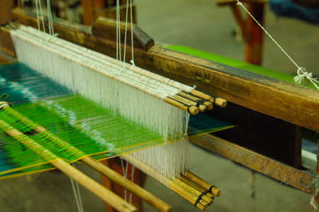 Hand made on a wooden loom manufacture of thread and fabric closeup Stock Photo