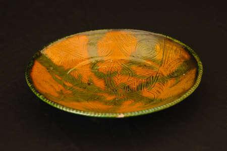 oriental antique ceramic plate on a black background closeup