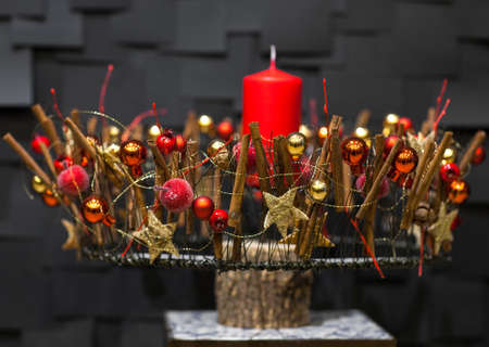decorative balls and stars decorated gold color red candle on a dark background with tiles for the new year