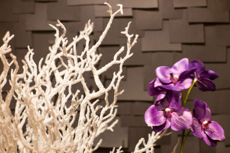 handmade artificial white a snowy branch with a purple flower on a dark background in the form of tiles