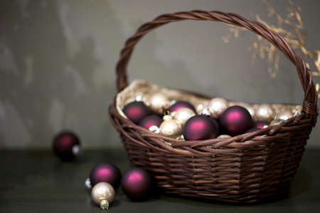 shiny and matt Christmas tree toys silver and pink colors in a wicker basket with a branch of the tree Stock Photo