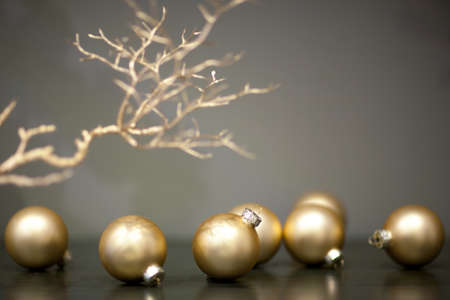 shiny and matt gold colored christmas tree toys and branch of a tree on a gray background