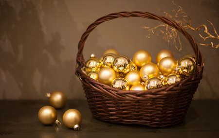 shiny and matt Christmas tree toys golden color in a wicker basket with a branch of the tree Stock Photo