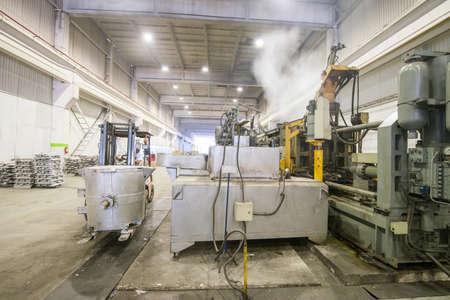 Verter el metal de aluminio desde la cuchara a la máquina de carga en un recipiente grande Foto de archivo - 66951327