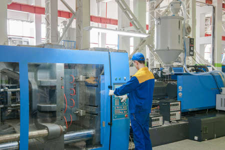 Industrial injection molding press machine for the manufacture of plastic parts using polymers in the management of worker Stok Fotoğraf - 67568464
