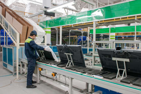 closeup line conveyor assembly and packing televisions in a workshop