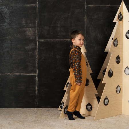 on a dark background little boy posing in a fashionable costume near a Christmas tree made of wood Stock Photo