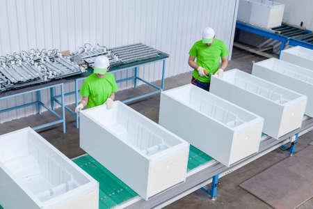 Suelo de fábrica para la producción y montaje de refrigeradores domésticos en la cinta transportadora. los trabajadores de la fábrica recogen refrigeradores en la cinta transportadora Foto de archivo - 70539695