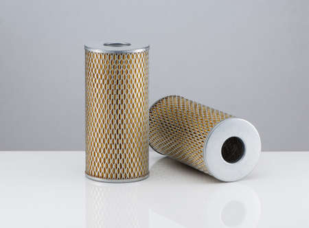 two automotive filter cylindrical shape  on a white background with reflection Stock Photo
