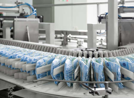 diapers on a conveyor belt closeup. factory and equipment for the production of pampers
