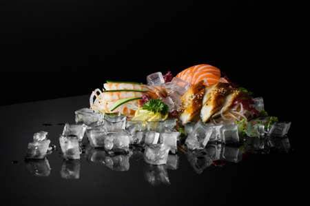 set of sushi with pieces of melting ice on a black background with reflection