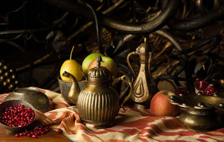 fruit and a metal jug with bowls in oriental style on the background of decorative forging ornament. still life in oriental style