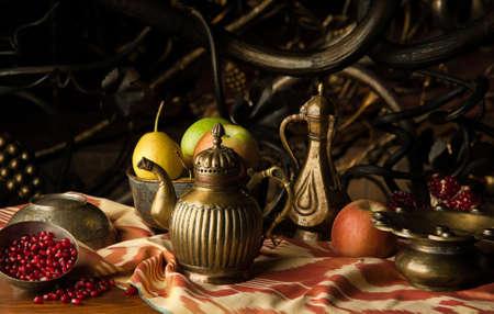 frutta e una brocca di metallo con ciotole in stile orientale sullo sfondo di ornamento decorativo forgiatura. natura morta in stile orientale