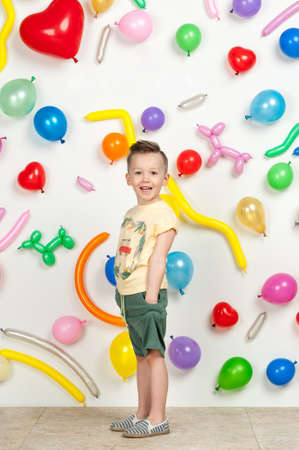 boy on a white background with colorful balloons. boy in a tank top and shorts on a white background with balloons in the shape of a heart Stockfoto