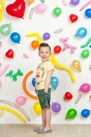 Niño sobre un fondo blanco con globos de colores. niño en una camiseta sin mangas y pantalones cortos sobre un fondo blanco con globos en forma de corazón Foto de archivo - 75352787
